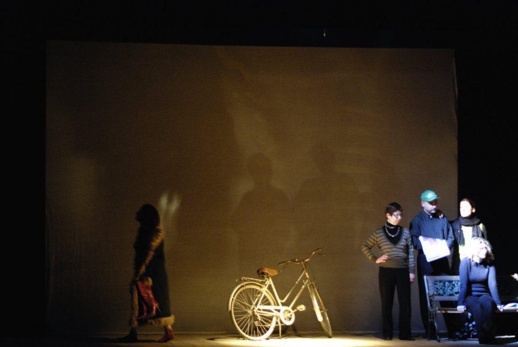 palco scena di insieme con 4 interpreti sulla destra, bicicletta al centro, mersia in uscita, effetto velatino